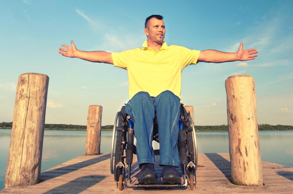 Persona con discapacidad en un muelle, disfrutando del verano.